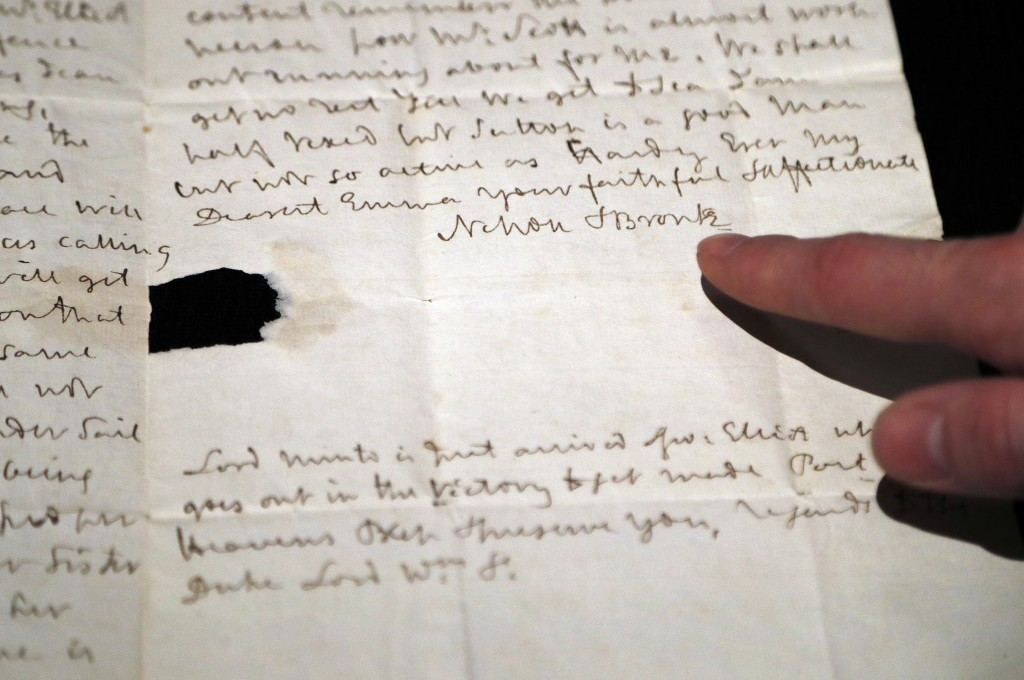 A Sotheby's employee points to a signature of Lord Nelson on a letter at Sotheby's auction house in London, Thursday, Jan. 11, 2018. An exceptionally