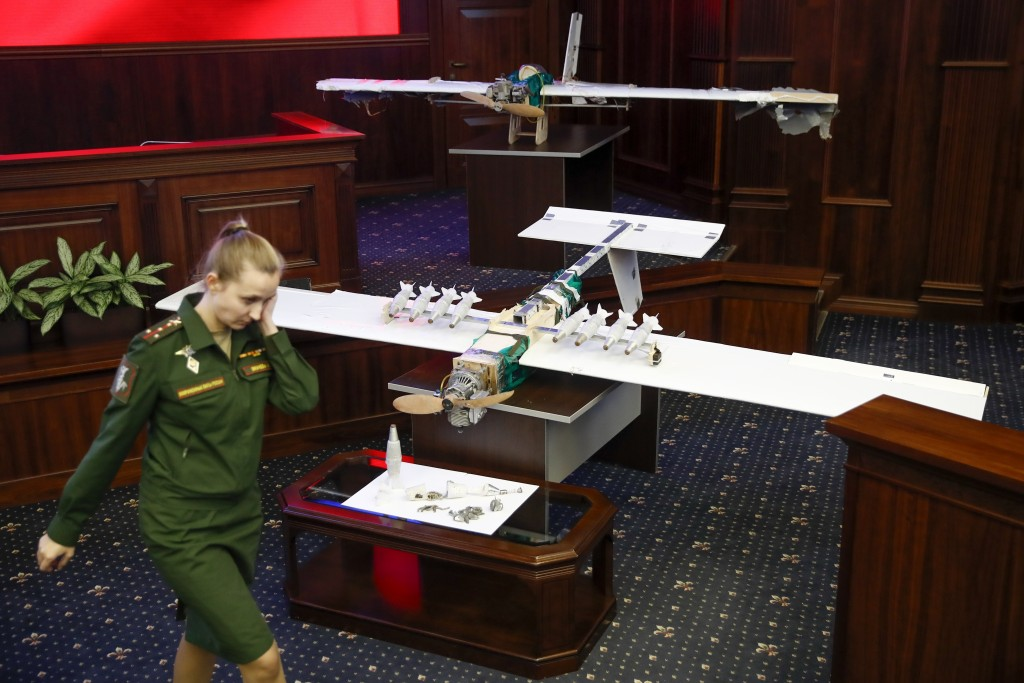 A Russian officer walks next to drones that attacked the Russian air base in Syria and were captured by the Russian military are displayed at a briefi