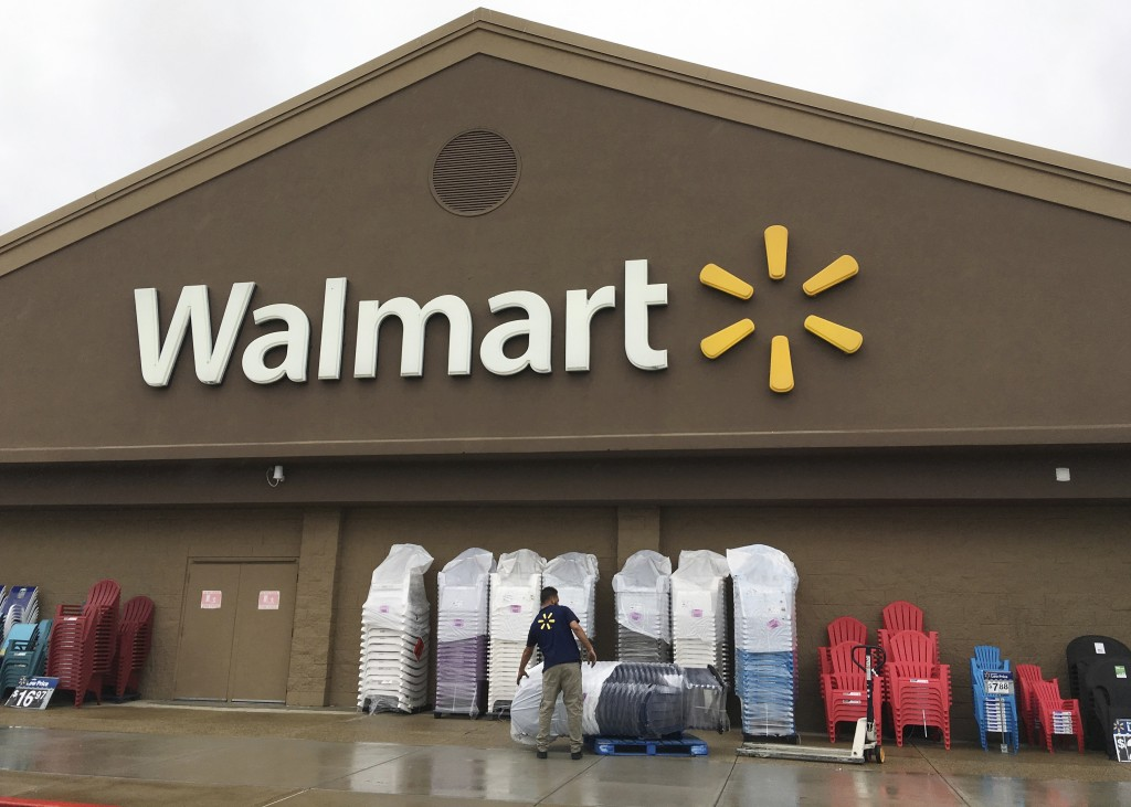 FILE - In this June 5, 2017, file photo, a worker stacks merchandise outside a Walmart in Salem, N.H. Walmart is boosting its starting salary for U.S.
