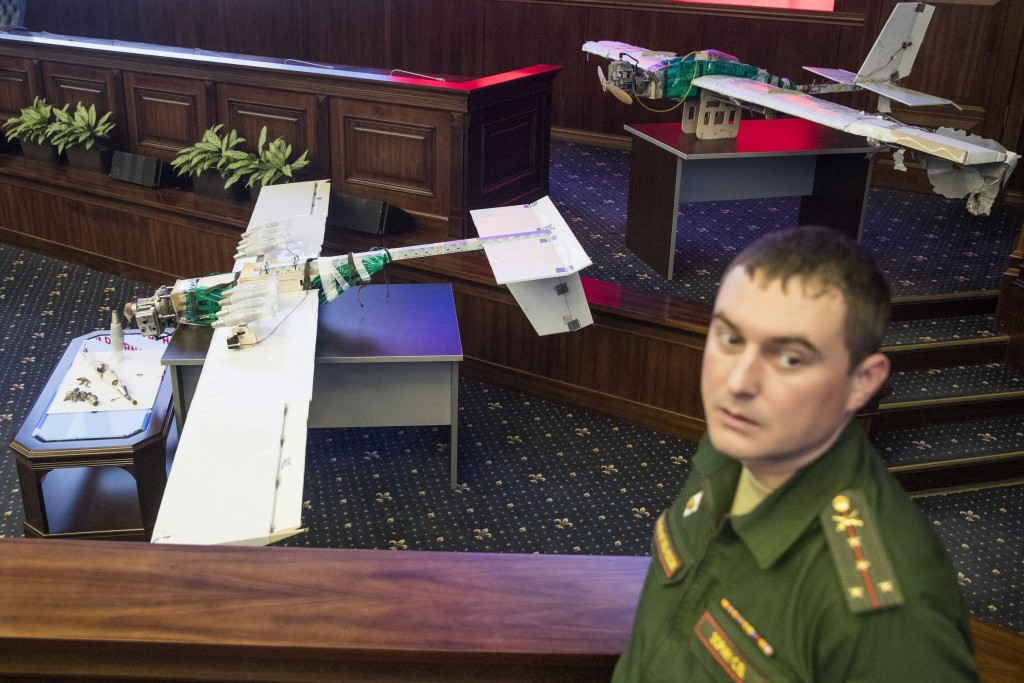 A Russian officer stands next to drones that attacked the Russian air base in Syria and were captured by the Russian military are displayed at a brief