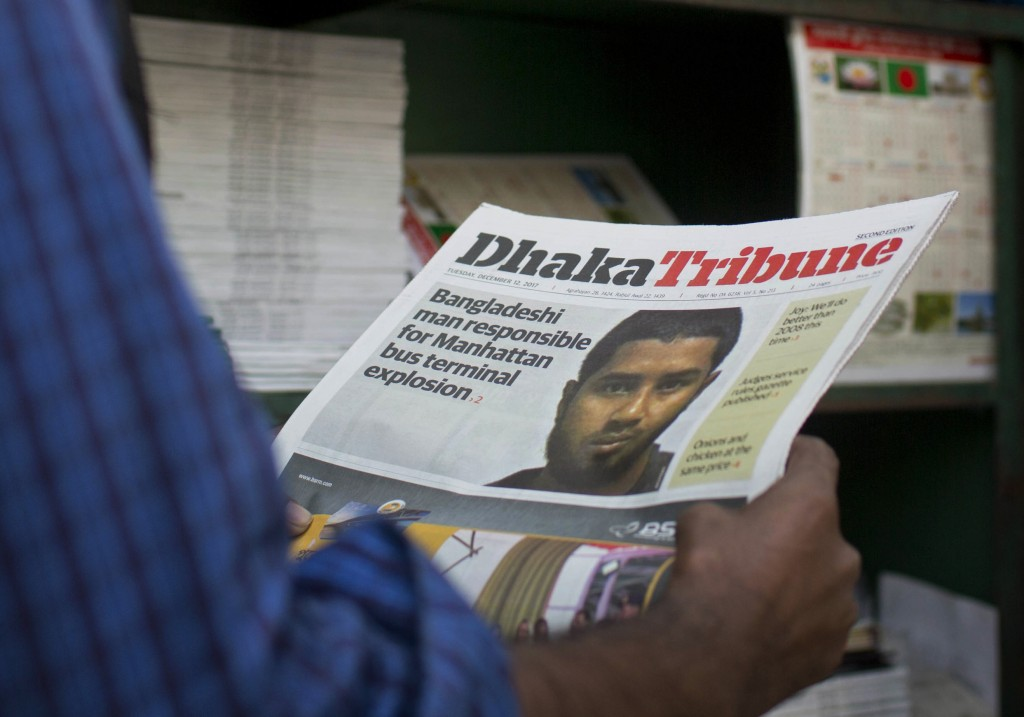 FILE - In this Dec. 12, 2017, file photo, a Bangladeshi man reads a national newspaper whose front pages shows the news of 27-year-old Bangladeshi man