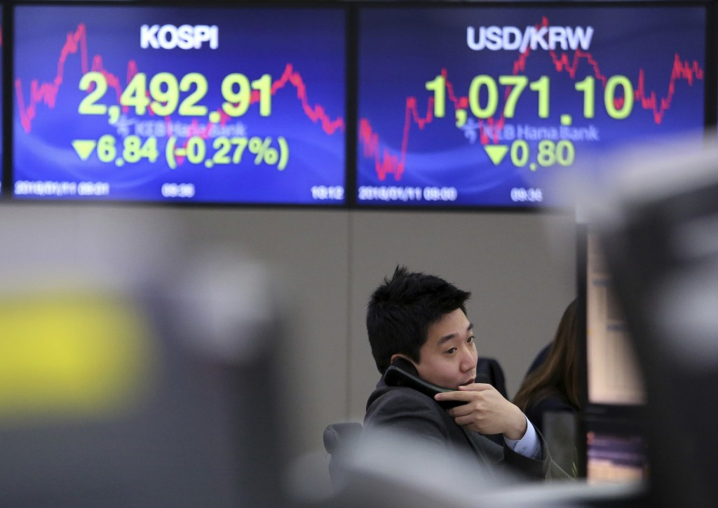 A currency trader talks on the phone at the foreign exchange dealing room of the KEB Hana Bank headquarters in Seoul, South Korea, Thursday, Jan. 11,