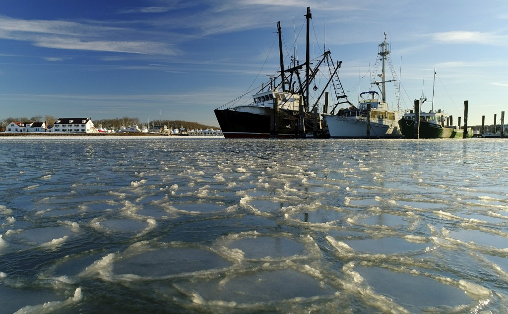 FILE - In this Jan. 7, 2018, file photo, fishing trawlers sit on the frozen harbor of Lake Montauk surrounded by thin sheets of ice in Montauk, N.Y. A...