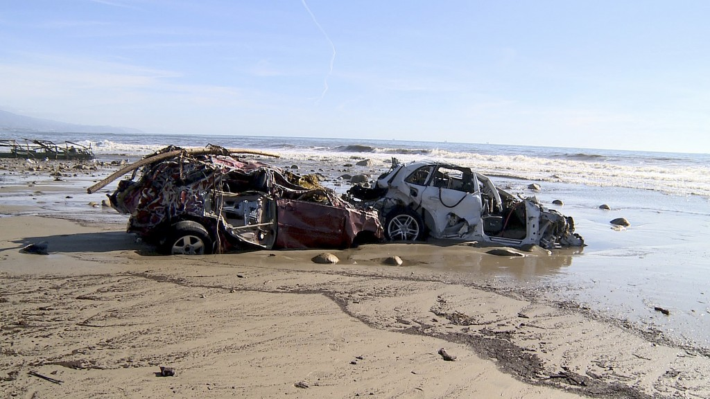 In this Wednesday, Jan. 10, 2018 still image from video, cars and debris that washed to the coast from storms and flooding are shown on a beach in Mon