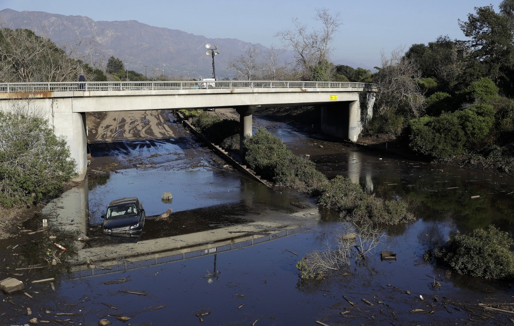 A car sits in flooded water on Highway 101 in Montecito, Calif., Thursday, Jan. 11, 2018. Rescue workers slogged through knee-deep ooze and used long