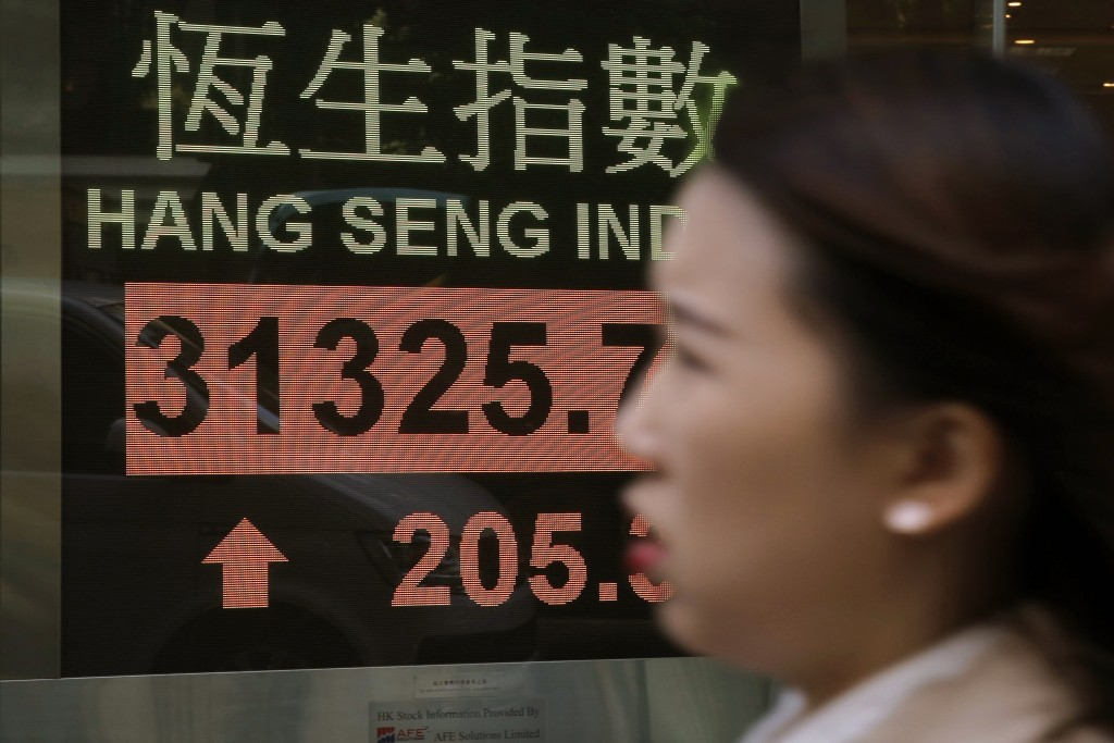 A woman walks past an electronic stock board showing the Hang Seng Index at a bank in Hong Kong, Friday, Jan. 12, 2018. Most Asian stocks markets were