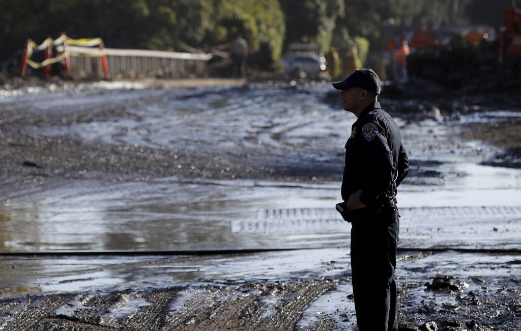 A California Highway Patrol officer stands in front of a road damaged from storms in Montecito, Calif., Thursday, Jan. 11, 2018. Rescue workers slogge