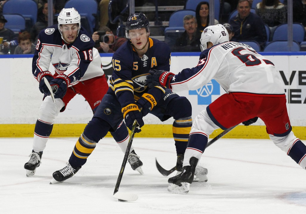 Buffalo Sabres forward Jack Eichel (15) controls the puck against Columbus Blue Jackets Pierre-Luc Dubois and Markus Nutivaara (65) during the first p