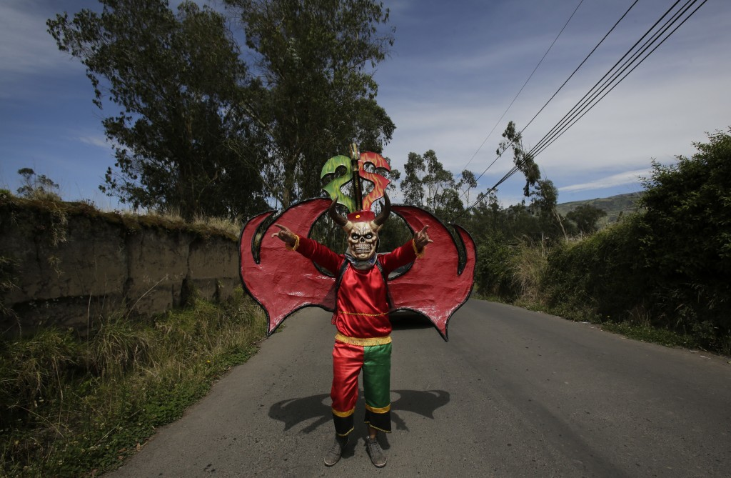 """In this Jan. 5, 2018 photo, dressed for the traditional New Year's festival known as """"La Diablada"""", a participant strikes a pose in Pillaro, Ecuador."""