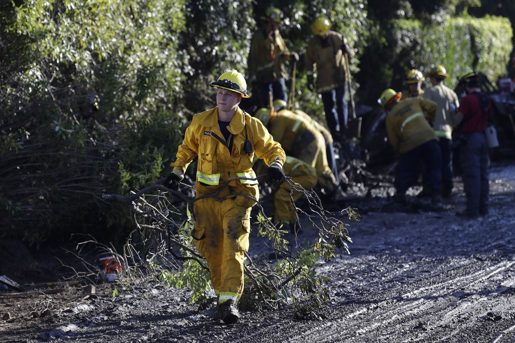 A firefighter cleans debris from an area damaged by storms in Montecito, Calif., Thursday, Jan. 11, 2018. Rescue workers slogged through knee-deep ooz