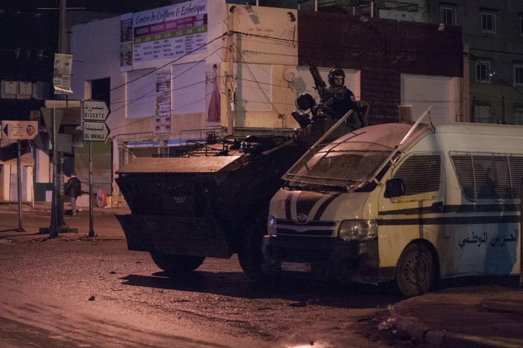 Security forces in an armoured vehicle patrol the district of Intilaka, north of Tunis, Tunisia, Thursday Jan. 11, 2018. Tunisian authorities say over