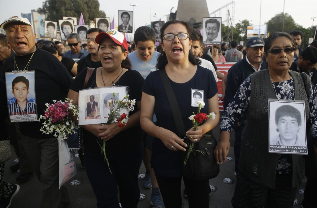 Demonstrators shouts slogans as they hold photographs of people disappeared during the government of former President Alberto Fujimori, in Lima, Peru,