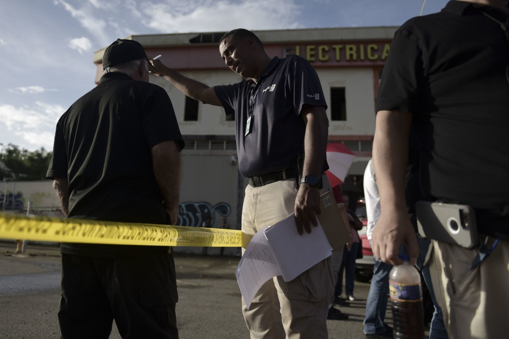 Forensic workers investigate a crime scene where a man was found fatally shot, in San Juan, Puerto Rico, Thursday, Jan. 11, 2018. Hurricane Maria has
