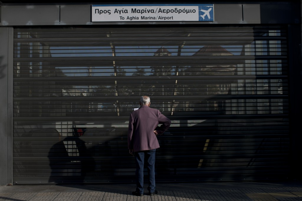 A man looks through the shuttered entrance of a metro station in the Egaleo suburb of Athens during a 24-hour strike, Friday, Jan. 12, 2018. Greek tra