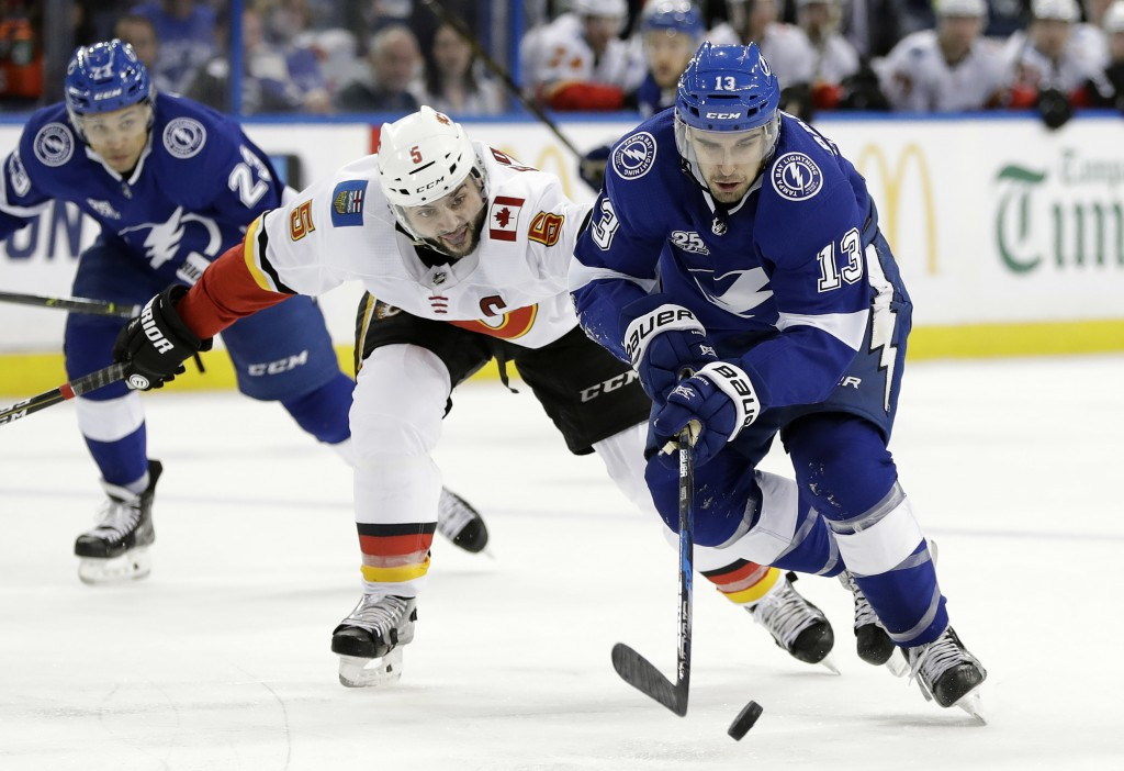 Tampa Bay Lightning center Cedric Paquette (13) gets around Calgary Flames defenseman Mark Giordano (5) during the second period of an NHL hockey game