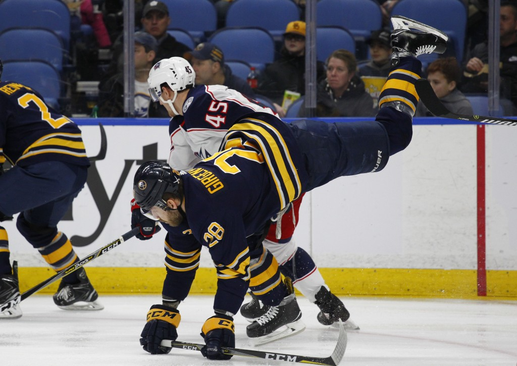 Buffalo Sabres forward Zemgus Girgensons (28) is tripped by Columbus Blue Jackets forward Lukas Sedlak (45) during the first period of an NHL hockey g