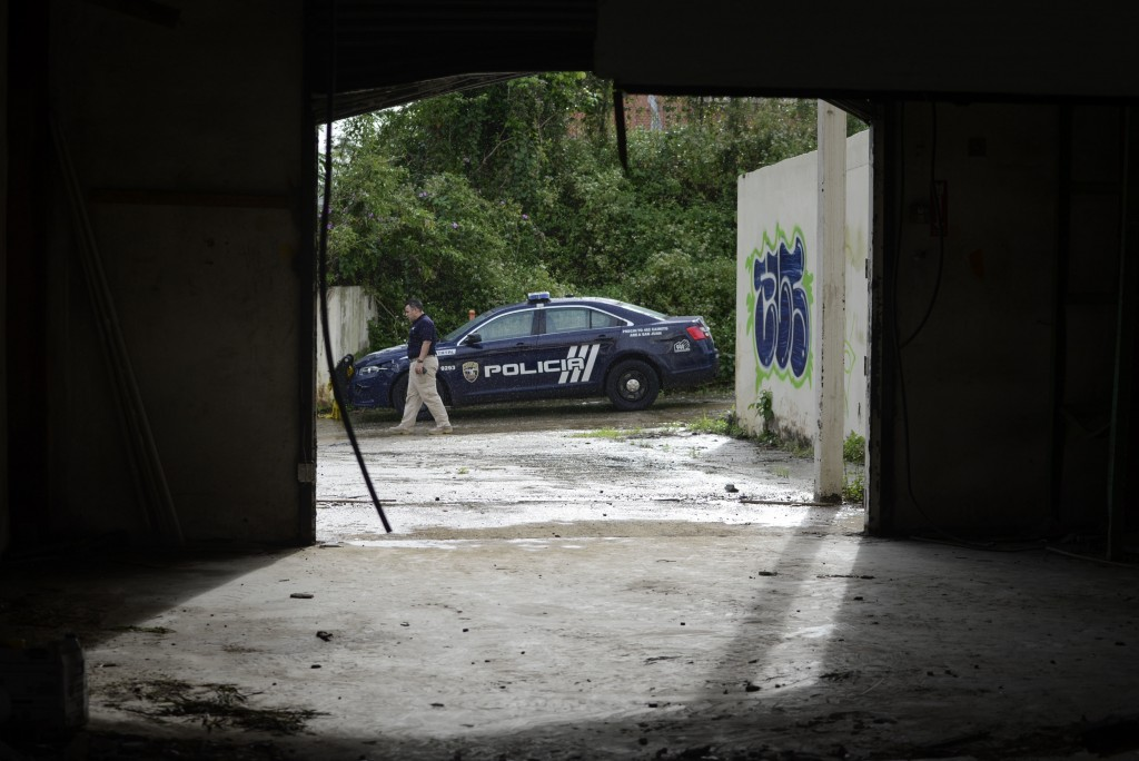 A police officer walks past his vehicle at a crime scene where a man was found fatally shot, in San Juan, Puerto Rico, Thursday, Jan. 11, 2018. Alread
