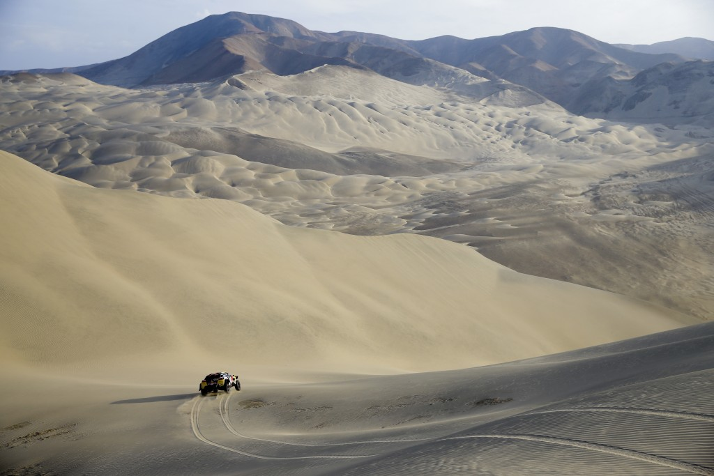 In this Jan. 10, 2018 photo, driver Stephane Peterhansel, of France, and co-driver Jean Paul Cottret, of France, race their Peugeot down a dune during