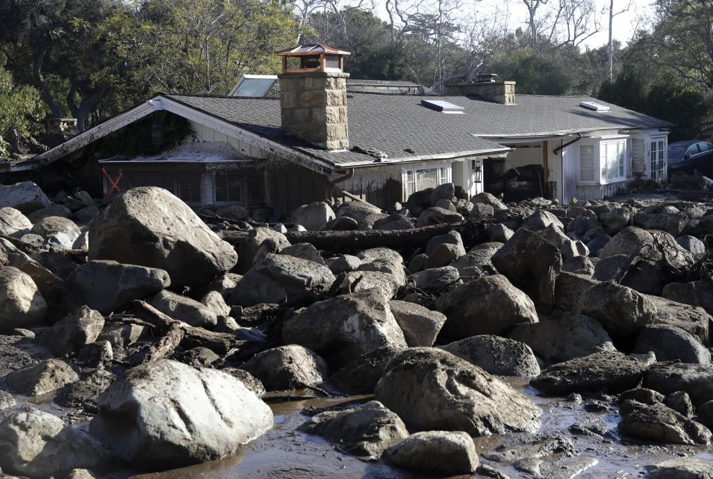 Large rocks and mud are shown in front of a house in Montecito, Calif., Thursday, Jan. 11, 2018. Hundreds of rescue workers slogged through knee-deep