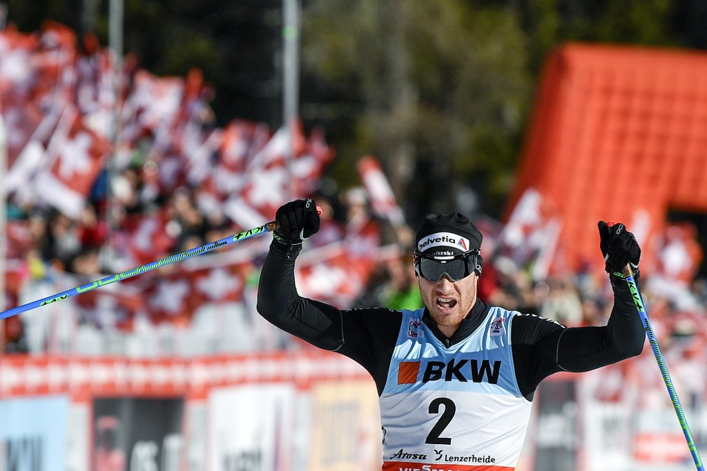 FILE - In this Jan. 1, 2018, file photo, winner Dario Cologna of Switzerland celebrates after crossing the finish line during the men's 15 kilometer c