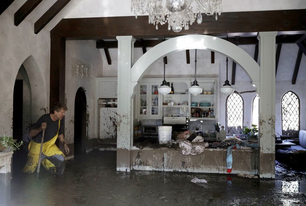 Bill Asher walks through mud in his home damaged by storms in Montecito, Calif., Thursday, Jan. 11, 2018. Rescue workers slogged through knee-deep ooz