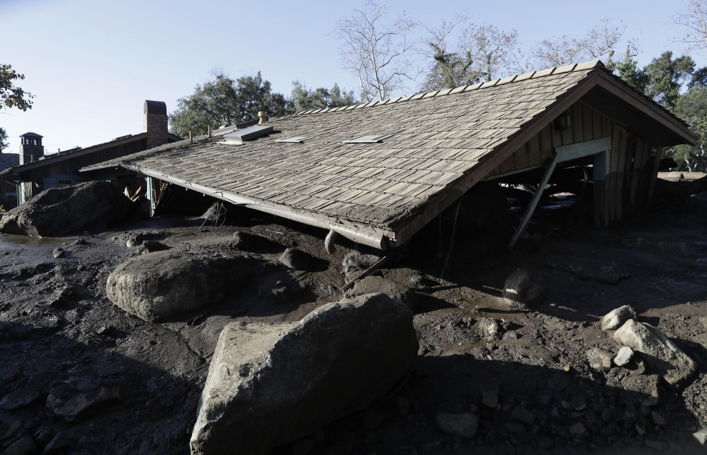 The roof of a structure damaged from storms sits over mud and rocks in Montecito, Calif., Thursday, Jan. 11, 2018.  Hundreds of rescue workers slogged