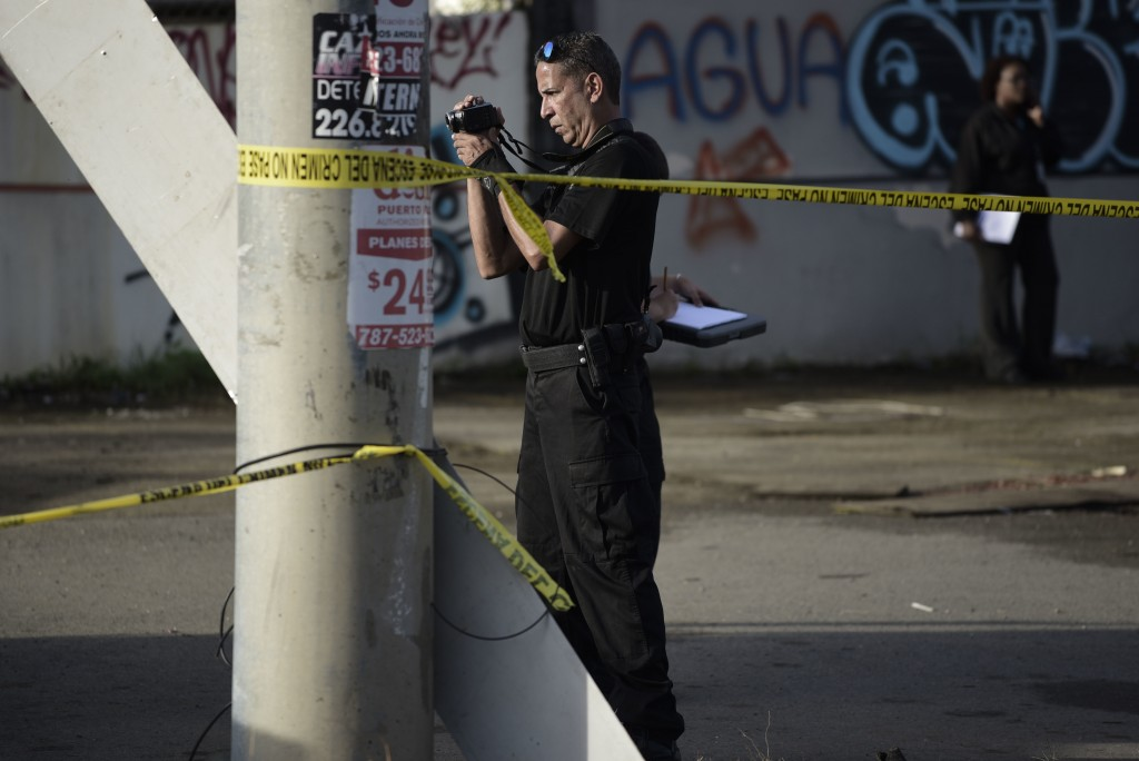 A forensic worker photographs a crime scene where a man was found fatally shot, in San Juan, Puerto Rico, Thursday, Jan. 11, 2018. Thirty-two people h