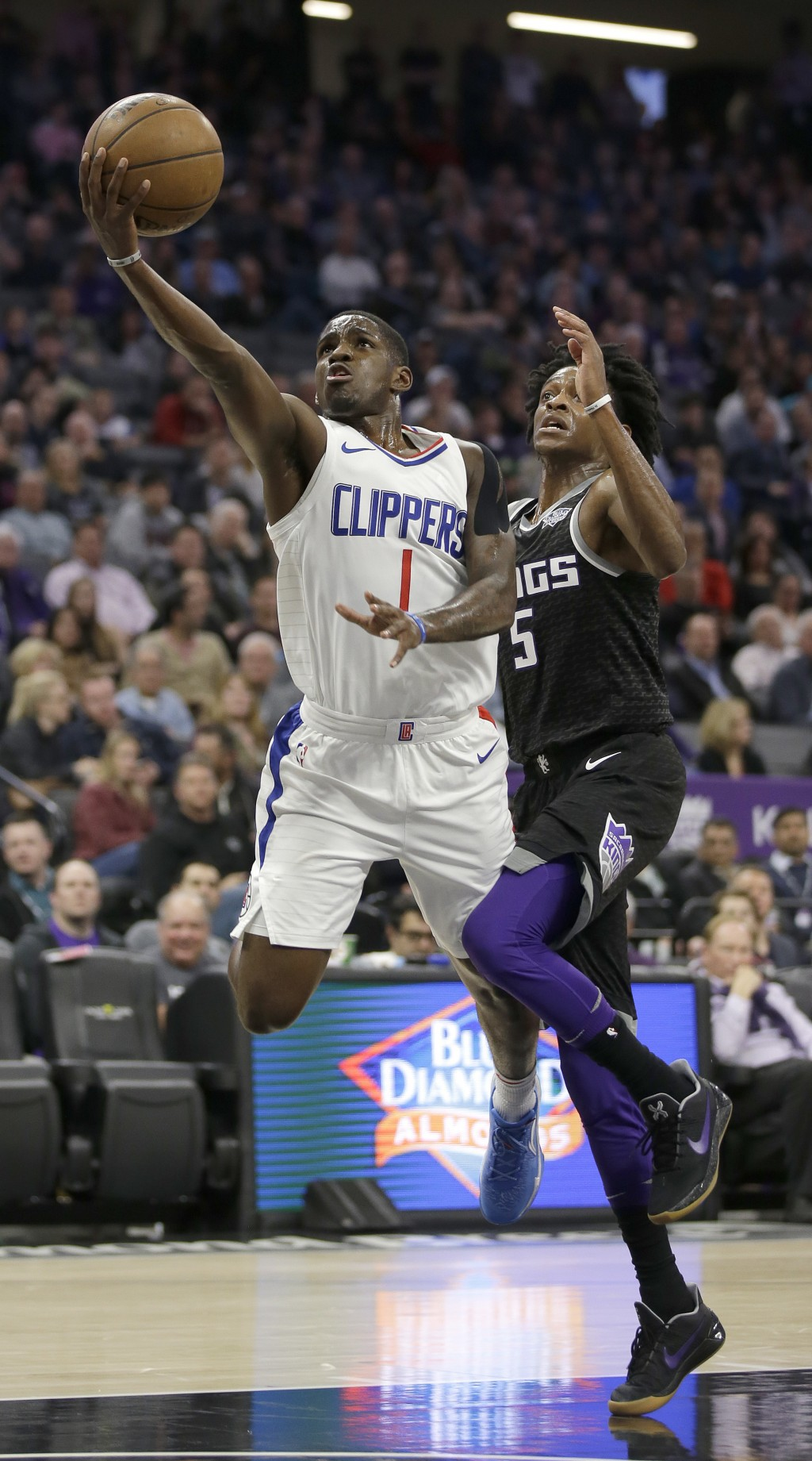 Los Angeles Clippers guard Jawun Evans, left, goes to the basket against Sacramento Kings guard De'Aaron Fox during the first quarter of an NBA basket