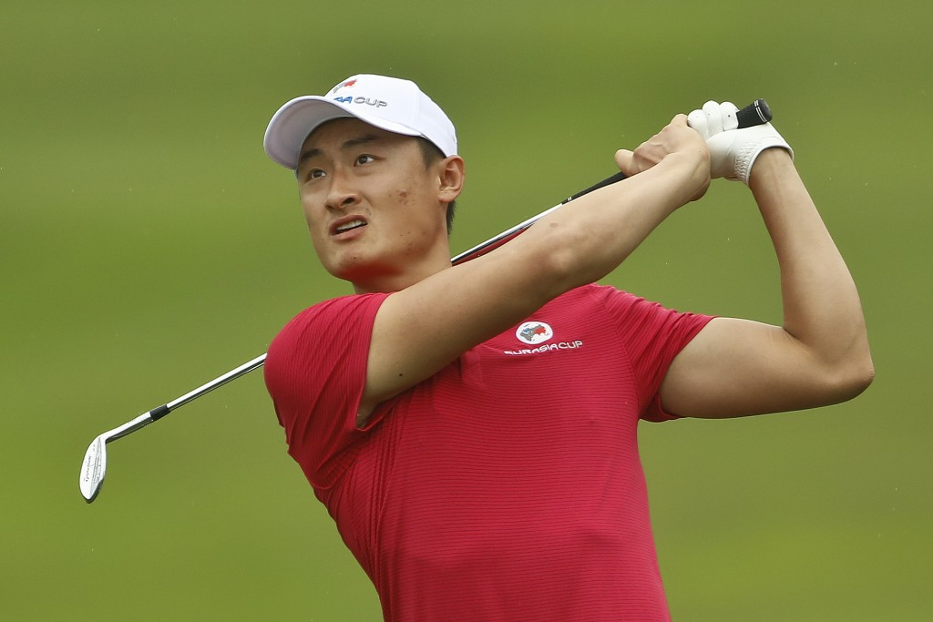Li Haotong of China watches his shot on the 8th hole during the four-ball matches of the 2018 EurAsia Cup golf tournament at Glenmarie Golf & Country