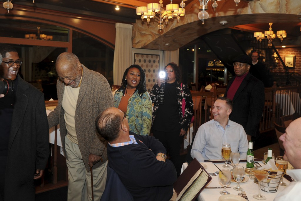 In this Wednesday, Jan. 10, 2018 photo, Bill Cosby passes other diners as he arrives for dinner at an Italian restaurant in Philadelphia. Cosby's new