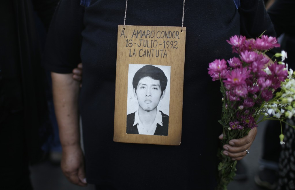 A demonstrator holds a photograph of a person disappeared during the government of former President Alberto Fujimori, in Lima, Peru, Thursday, Jan. 11
