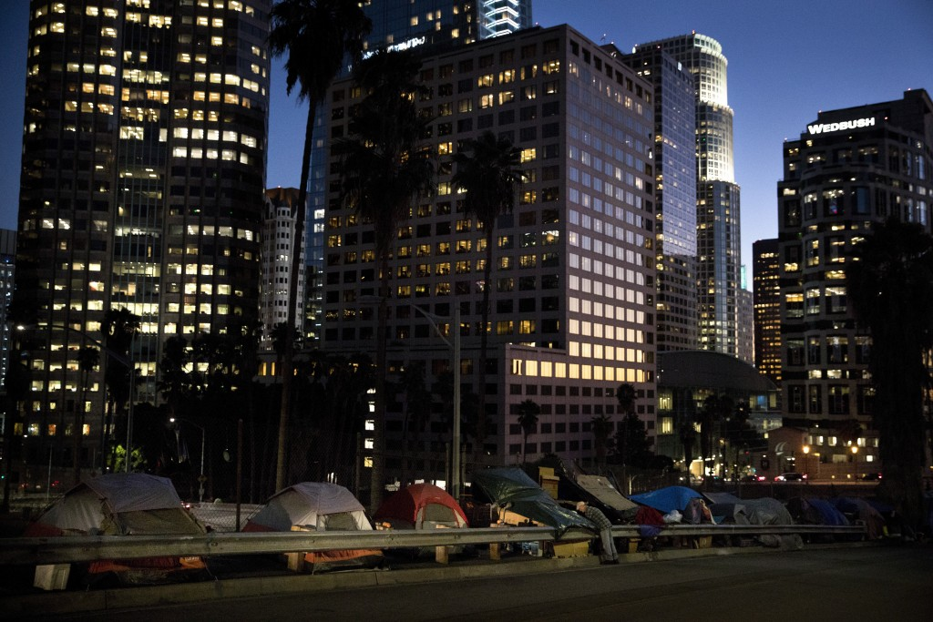 FILE - In this Dec. 1, 2017 file photo, homeless tents are dwarfed by skyscrapers as 63-year-old Vincent, who only gave his first name, sorts his belo