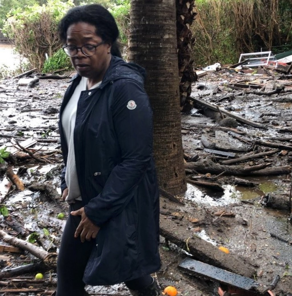 This Wednesday, Jan. 10, 2018, photo provided by Oprah Winfrey shows Winfrey standing in debris and mud flow as she looks at her neighbors property in