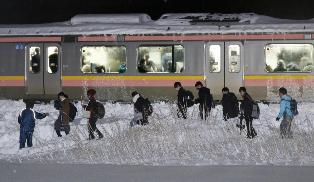 Passengers of a stranded train walk beside a railway track in Sanjo, Niigata prefecture, north of Tokyo early Friday, Jan. 12, 2018. A Japanese railwa