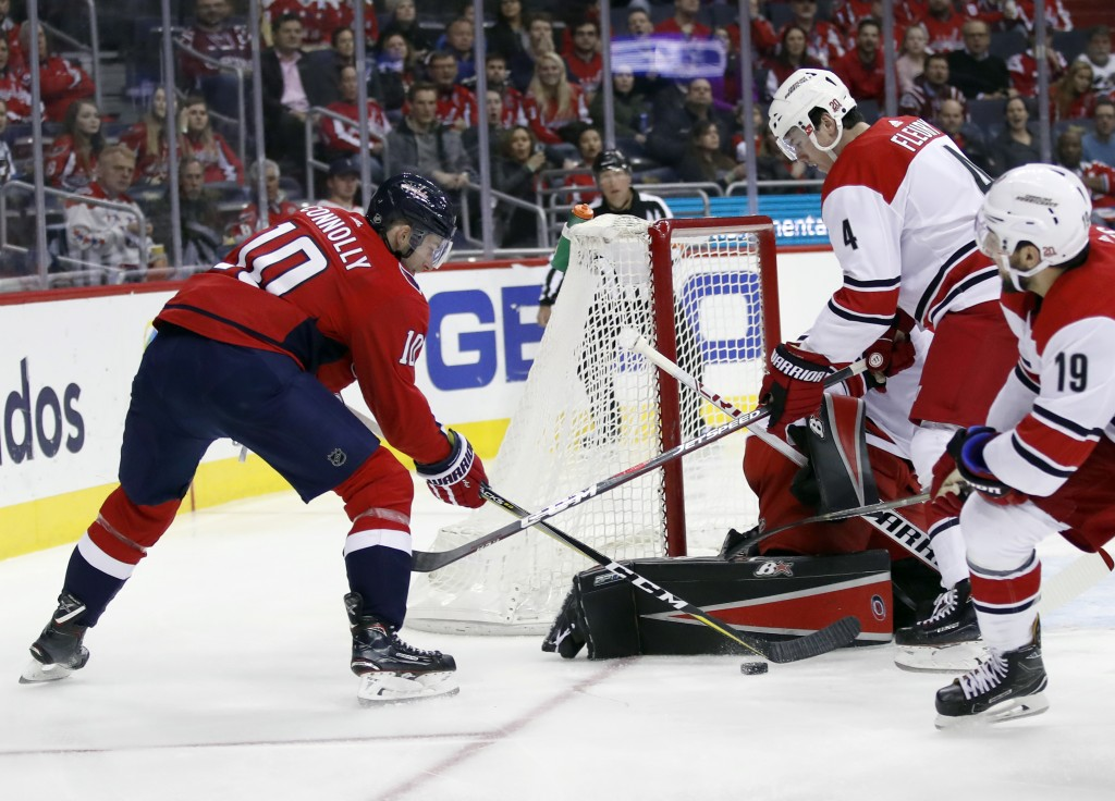 Washington Capitals right wing Brett Connolly (10) tries to shoot as Carolina Hurricanes goalie Scott Darling (33) and defenseman Haydn Fleury (4) def