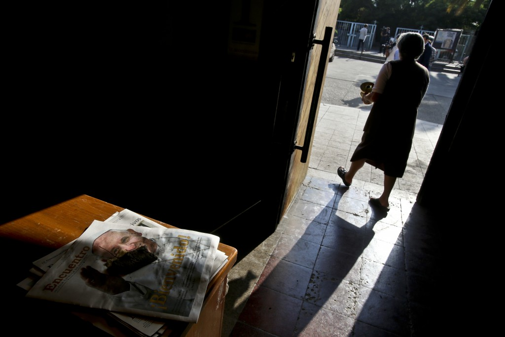 A church employee walks past a door damaged in an overnight firebomb attack at the Santa Isabel de Hungria Catholic Church, in Santiago, Chile, Friday