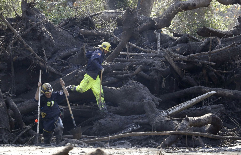 Emergency crew members work on storm damage in Montecito, Calif., Thursday, Jan. 11, 2018. Rescue workers slogged through knee-deep mud and used long