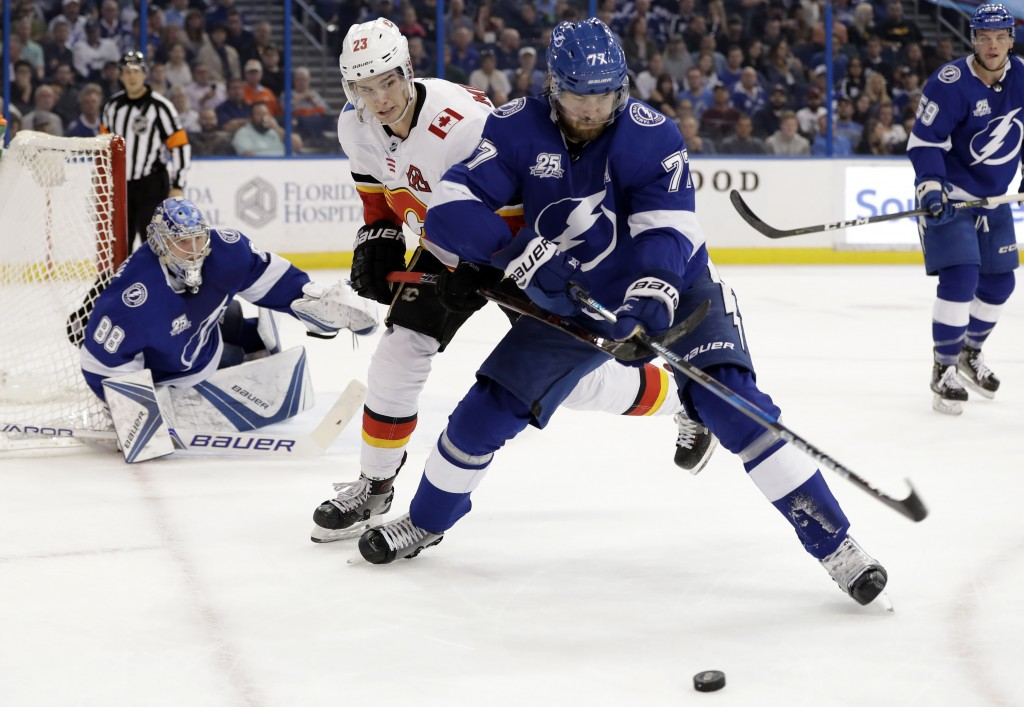 Tampa Bay Lightning defenseman Victor Hedman (77), of Sweden, beats Calgary Flames center Sean Monahan (23) to the puck in front of goaltender Andrei