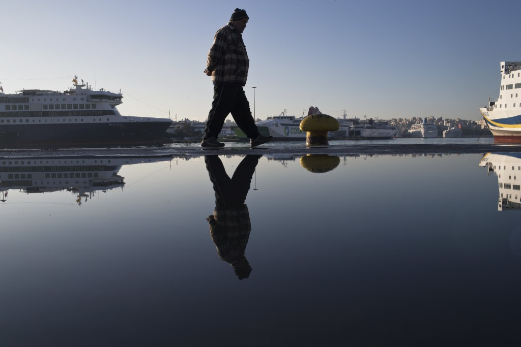 A man walks in front of docked ferries at the port of Piraeus near Athens during a 24-hour strike, Friday, Jan. 12, 2018. Greek transport workers, doc