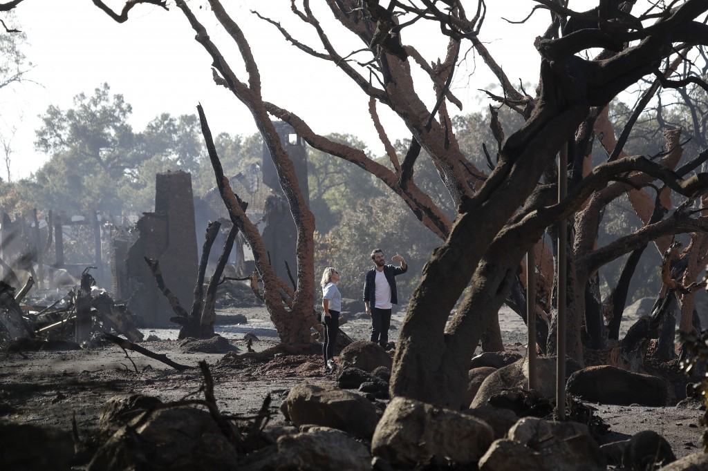 A woman and a man stand in front of a structure damaged from storms in Montecito, Calif., Thursday, Jan. 11, 2018.  Hundreds of rescue workers slogged
