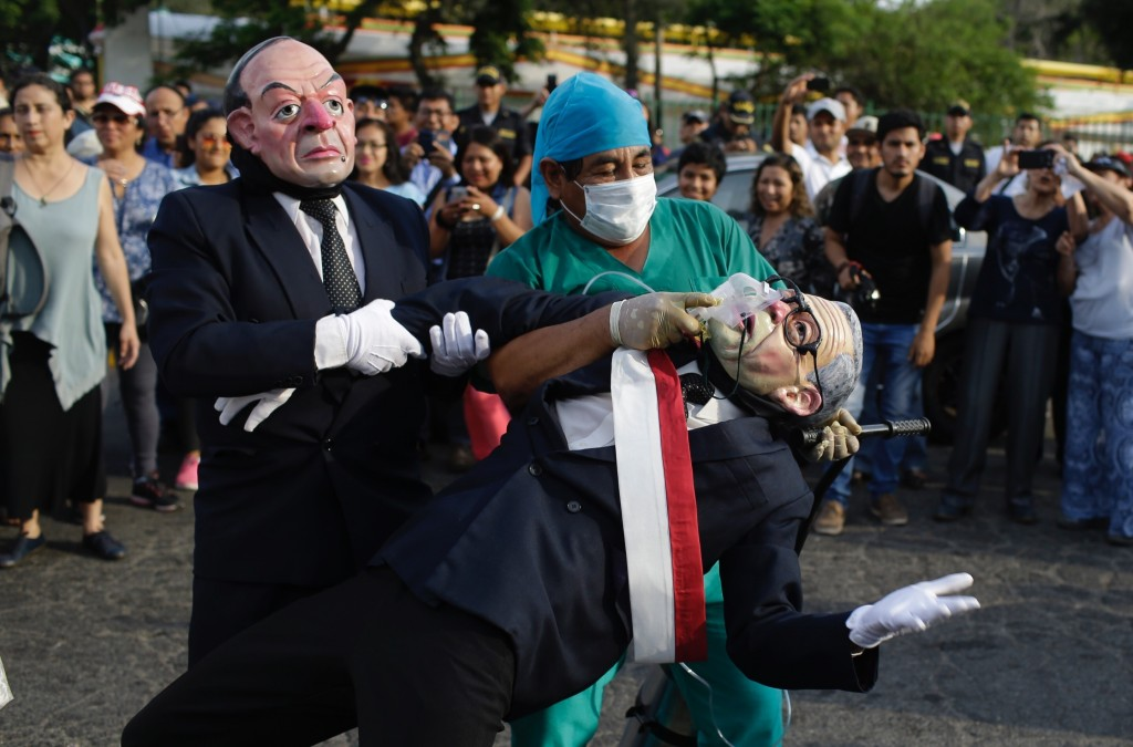 Actors wearing masks depicting former president Alberto Fujimori and former spy-chief Vladimiro Montesinos, left, perform during protest against the m