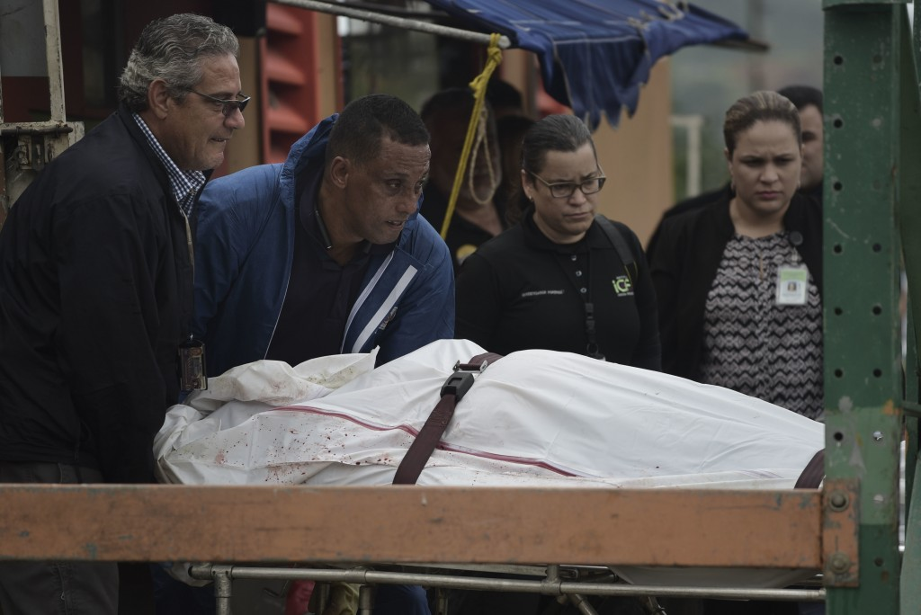 In this Thursday, Jan. 11, 2018 photo, forensic workers remove the body of a man found fatally shot in San Juan, Puerto Rico. As the Island struggles