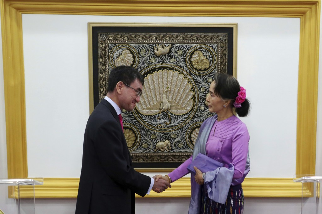 Myanmar's State Counselor and Foreign Minister Aung San Suu Kyi, right, shakes hands with Japanese Foreign Minister Taro Kono after their joint press