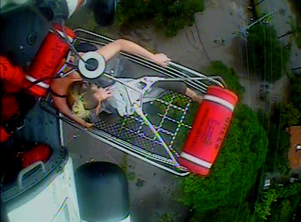 In this Jan. 9, 2018 image from video provided by the U.S. Coast Guard, a woman and an infant are hoisted aboard a Coast Guard helicopter as they are