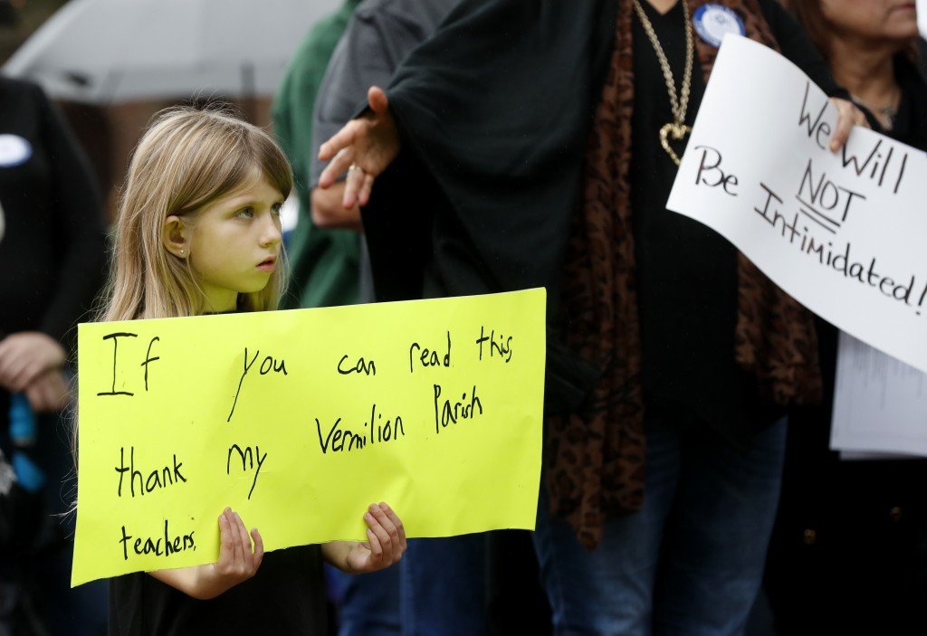 Sydney Brown, 6, holds a sign at a rally for school teacher Deyshia Hargrave, who was arrested while speaking against the superintendent's pay raise a