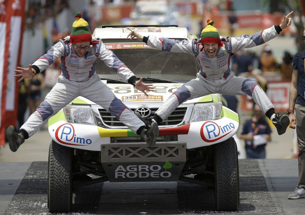 In this Jan. 6, 2018 photo, Zala Vaidotas, right, and his co-driver Jurgelenas Saulius, both of Lithuania, jump in unison on the podium ramp during th