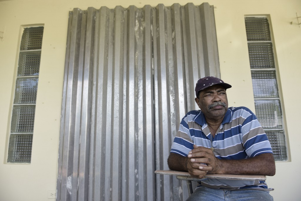 In this Tuesday, Jan. 9, 2018 photo, retiree Ramon Santiago sits on his front porch, less than a block away from where three bodies were discovered cr