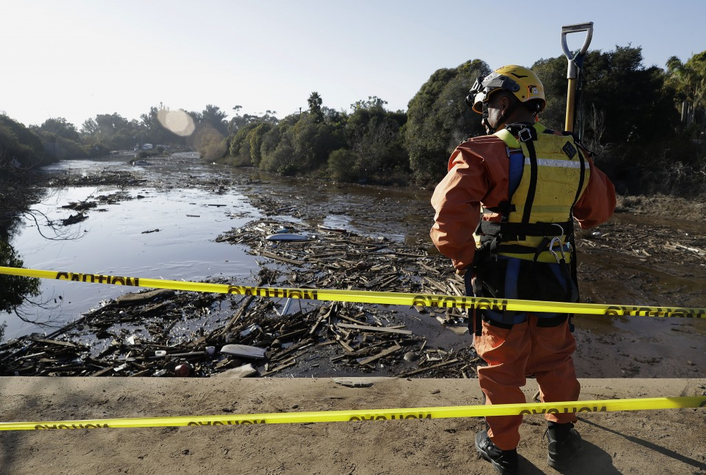 An emergency worker looks down from an overpass toward a flooded area of Highway 101 in Montecito, Calif., Thursday, Jan. 11, 2018. Rescue workers slo