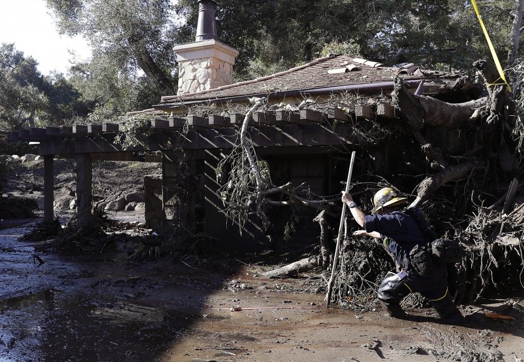 Alex Broumand of the Montecito Fire Department walks in mud in front of homes damaged from storms in Montecito, Calif., Thursday, Jan. 11, 2018. Rescu