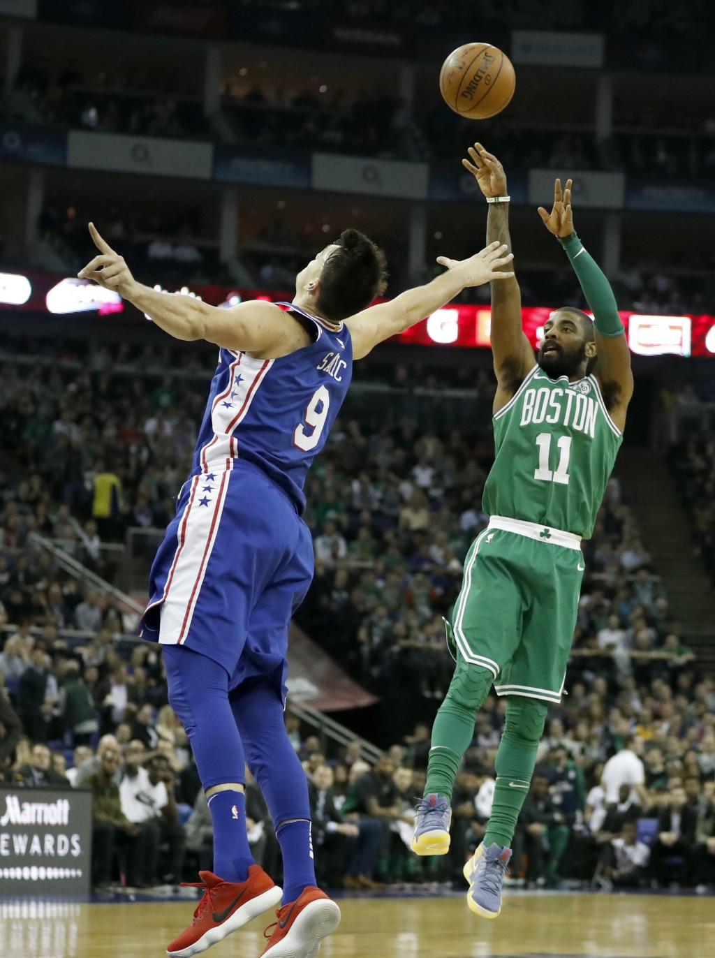 Philadelphia 76ers forward Dario Saric, left, goes up to block Boston Celtics guard Kyrie Irving as he shoots during an NBA basketball game between th